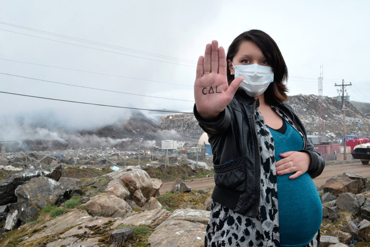 Iqaluit's Julie Alivaktuk is expecting her first child in 10 days. She's frustrated with how smoke from the dump is impacting her health and worries about how it will affect her baby. The word on her hand reads,