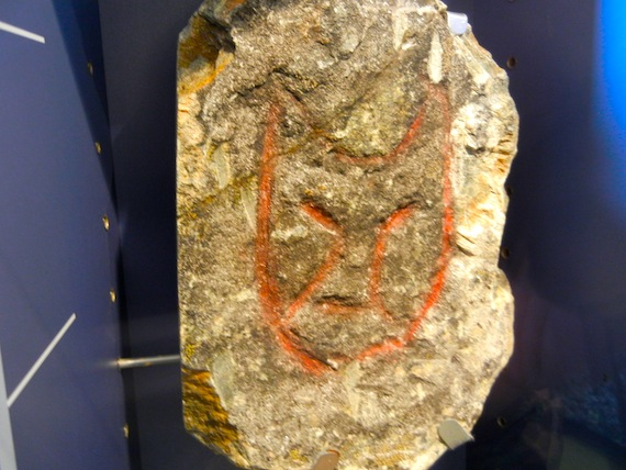 A cat-like face peers from a rock on display at the Pingualuit provincial park's visitors centre in Kangiqsujuaq in 2010. The engraving, collected in the 1960s, hails the nearby island of Qajartalik. (PHOTO BY JANE GEORGE)