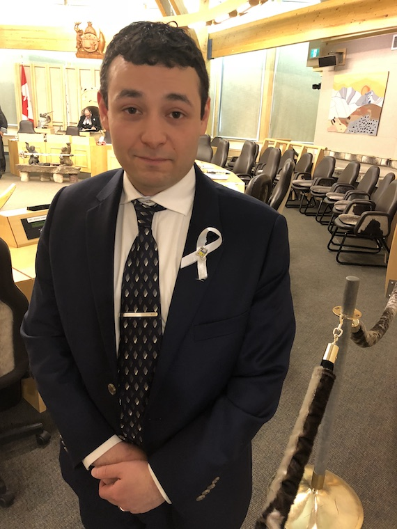Nunavut MLA Adam Arreak Lightstone, who represents the riding of Iqaluit-Manirajak, stands in the territorial assembly chamber on June 7, the seventh anniversary of the violent death of his sister Sula Enuaraq, along with that of her two daughters. You can see the white lapel ribbon, a symbol of the movement of men and boys against domestic violence. (PHOTO BY JANE GEORGE)