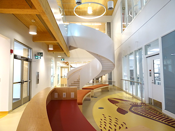 A spiral staircase beckons upward at the end of this unoccupied hall on the first floor of the main science building. The artwork on the floor,