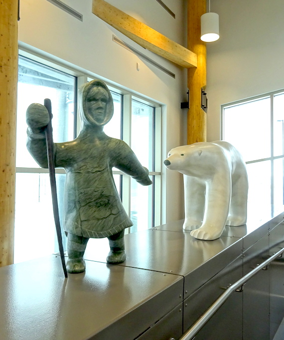 This piece by Koomuatuk (Kuzy) Curley of Cape Dorset is named Ningiuq amma Nanuq (Elder and Polar Bear). It portrays the story of a grandmother who adopted a bear cub, which then grew up.