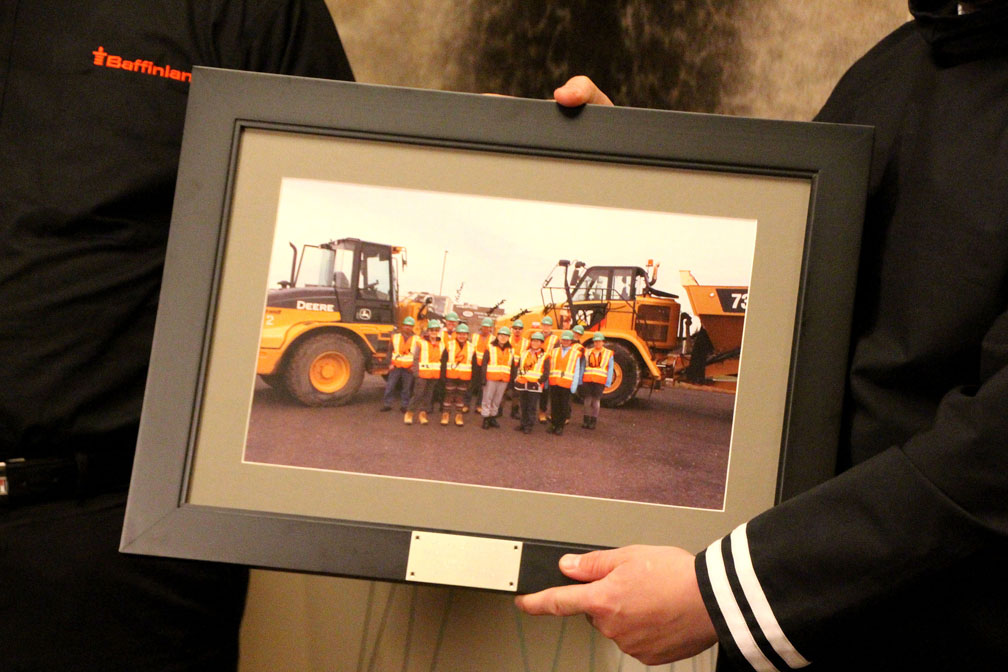 At a signing ceremony held on Oct. 3 for their amended Inuit impact and benefits agreement, Brian Penney, the president and CEO of Baffinland Iron Mines Corp., and P.J. Akeeagok, the president of the Qikiqtani Inuit Association, display a photo of Inuit heavy-equipment trainees who have benefited from a training program recently struck between QIA and the company. QIA, along with the Hamlet of Pond Inlet and the Mittimatalik Hunters and Trappers Organization, told Northern Affairs Minister Dominic LeBlanc that such training programs would be threatened if the Mary River iron mine cannot increase its production. (PHOTO BY BETH BROWN)