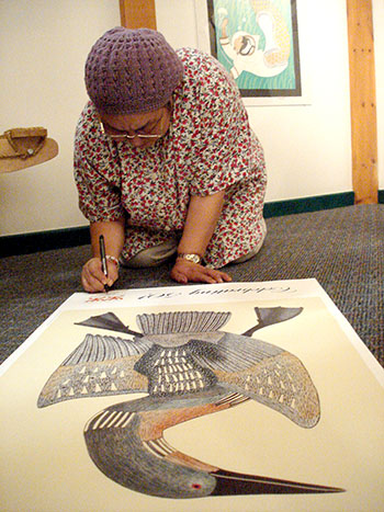 Mayoreak Ashoona, 63, a Cape Dorset artist who now lives in Iqaluit, autographs a poster of