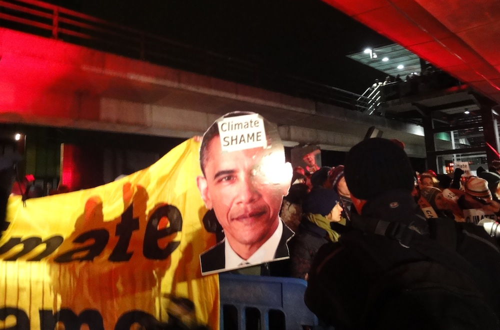 "During the early hours of Dec. 19, protesters gathered outside an entrance to the Bella Centre chanting ""shame, shame"" and ""bad deal, no deal,"" while brandishing a larger-than-life-size image of U.S. president Barack Obama. (PHOTO BY JANE GEORGE)"