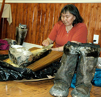 A Kangiqsujuaq woman shows a group of officials from Quebec's tourism department how to clean a sealskin. (PHOTO BY SARAH ROGERS)