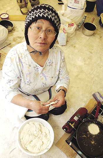 A woman takes part in a bannock-making competition during the 2003 version of Toonik Tyme in Iqaluit. (FILE PHOTO)