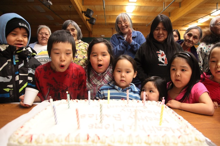 Elders watch March 18 as children gather to help blow out the candles on a cake celebrating the return of birthing to Cambridge Bay. (PHOTO BY BILL BRADEN, COURTESY OF NUNAVUT HSS)