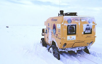 Moon-1 struggles through deep snow as it follows its snowmobiling guides across the sea ice.