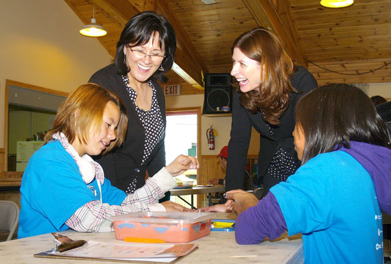 Leona Aglukkaq, the federal health minister and Nunavut's MP, and Jennifer Flanagan, the president and CEO of Actua science camps, watch kids at Iqaluit's parish hall do an activity July 14. Aglukkaq annouced $600,000 in federal funding over three years to support the Actua camps, which take place in nearly a dozen communities across Nunavut. (PHOTO BY CHRIS WINDEYER)