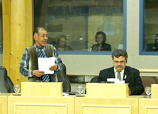 Nunavut's languages minister Louis Tapardjuk speaks in the Legislative Assembly Oct. 26 while Community and Government Services minister Lorne Kusugak listens. Tapardjuk came under fire for announcing the Government of Nunavut will delay implementation of two major pieces of language legislation. (PHOTO BY CHRIS WINDEYER)