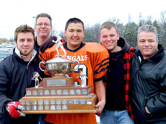 Brandon Lyta, centre, holding the A Cup championship trophy that his team, the Orleans Bengals, won Oct. 31. (PHOTO COURTESY PITSULALA LYTA)