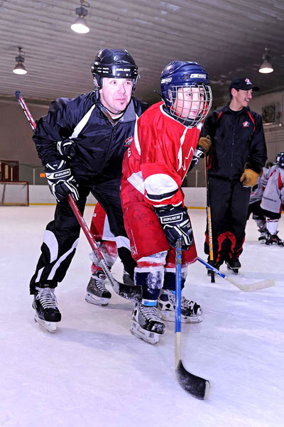 Hockey Canada coach Eric Couture works with player Elyassie Annanack. Hockey Canada's skills development camp visits a different Nunavik community every winter. (PHOTO BY PASCAL POULIN)