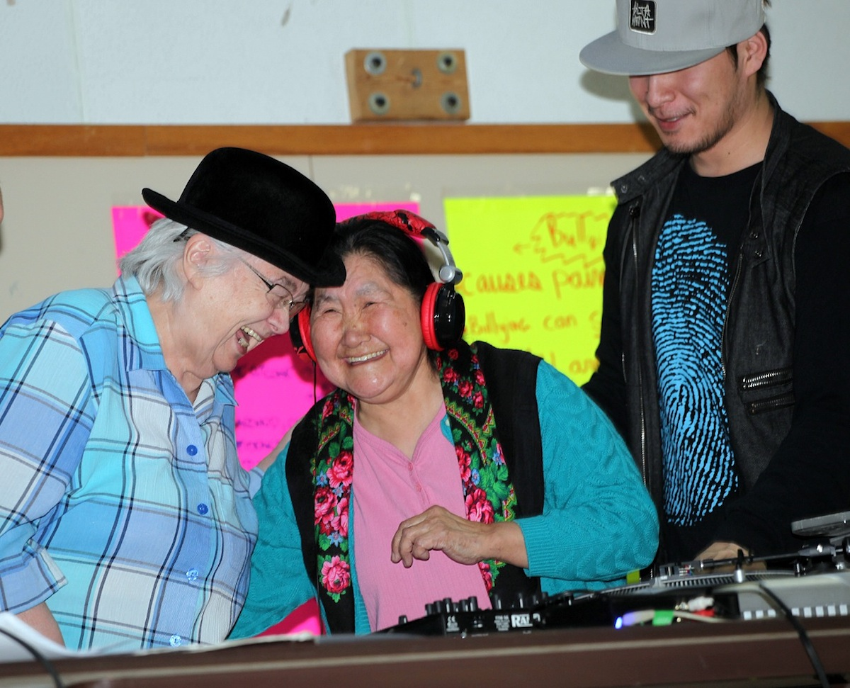 "Elder ""DJ""s Dorothy Mesher and Sapina Adams start to laugh as they spin the turntable at the March 11 show capping a week of hip hop in Kuujjuaq— something Blue Print For Life organizers encourage because it shows older people can be open to learning new things from youth. (SUBMITTED PHOTO)"
