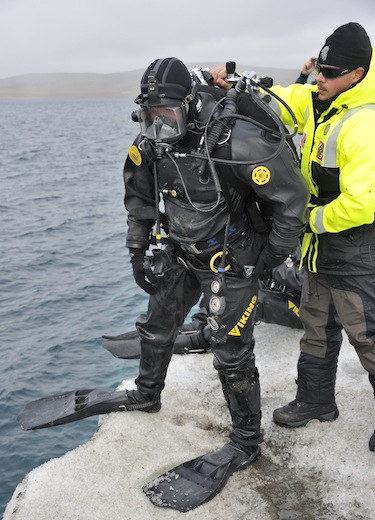 Petty Officer First Class William Roberts, with the United States Coast Guard, helps a fellow American Coast Guard diver prepare to enter the waters off of an iceberg that is being used as a diving platform during Op Nanook. (PHOTO BY SGT. NORM MCLEAN/CANADIAN FORCES COMBAT CAMERA/DND)