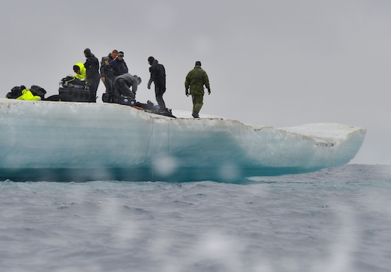 Canadian military divers and United States Coast Guard members wait on an iceberg in Resolute Bay, Nunavut, for the remainder of their team to arrive by a rigid hulled inflatable boat during Op Nanook. (PHOTO BY SGT. NORM MCLEAN/CANADIAN FORCES COMBAT CAMERA/DND)