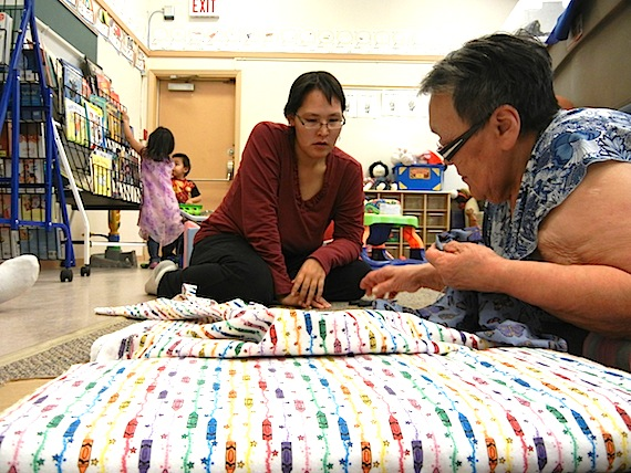 Michelle Maniyogena and Margaret Okina discuss how to cut a piece of cloth. Pregnant women and young mothers regularly get together with elders for sewing sessions organized by the Wellness Centre in Cambridge Bay. (PHOTO BY JANE GEORGE)