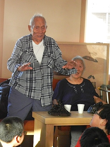 Moses Koihok, who at 91 is the oldest resident of Cambridge Bay, talks to Grade Seven students from Kiilinik High School at Cambridge Bay's Elders Palace on Oct. 6. Students meet with elders once a month for an afternoon there. The group shares a snack and students ask elders questions about how life was when they were young. (PHOTO BY JANE GEORGE)