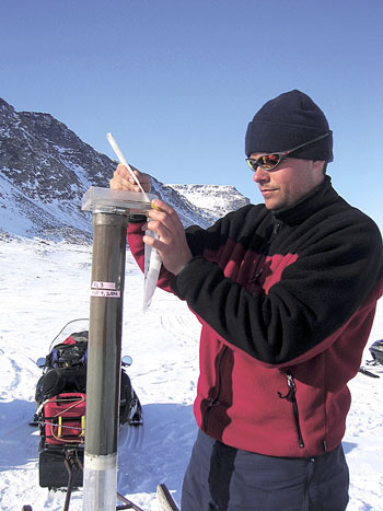 A researcher takes an ice-core sample from a site on Baffin Island in 2005. (FILE PHOTO)