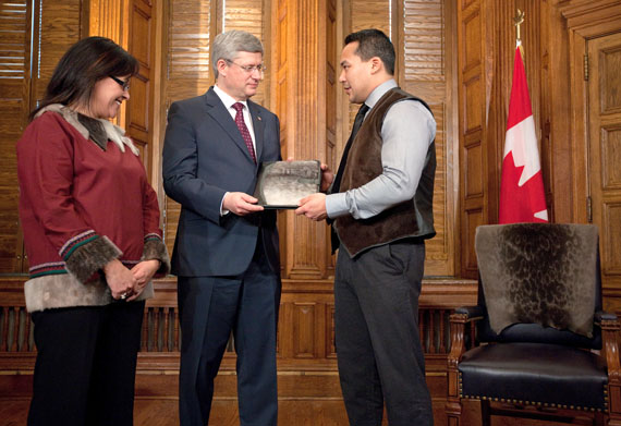 Pujjuut Kusugak, the mayor of Rankin Inlet, gives Prime Minister Stephen Harper a sealskin notebook Feb. 2 as Nunavut MP Leona Aglukkaq looks on, in a public relations event held as part of