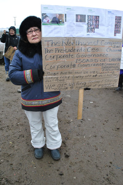 Veronica Dewar of Iqaluit carries a sign bearing a message about the CEO and board of directors of the North West Co. (PHOTO BY JIM BELL)