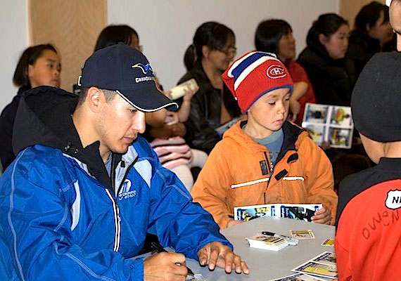 Jordin Tootoo of the Nashville Predators, also a spokesperson for Canadian North, signs autographs earlier this week in Arctic Bay during his tour of Nunavut's Baffin communities. Tootoo is scheduled to be in Qikiqtarjuaq and Pangnirtung on June 29 and in Iqaluit for June 30. (PHOTO BY CLARE KINES)