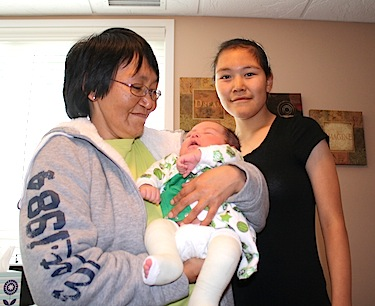 Rosie Evetalegak, 42,  holds her one-month-old grandson Cody Evetalegak, alongside her daughter Dana, 17, all from Cambridge Bay. (PHOTO BY ANGELA BRUNSCHOT)