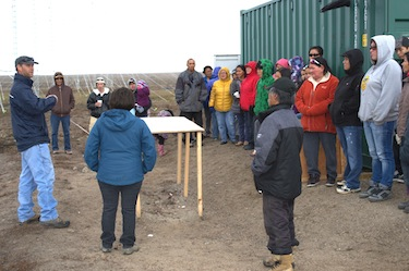 A group of people from Clyde River listen to engineer Jan Wiid speak about the radar towers installed near their community which will help track