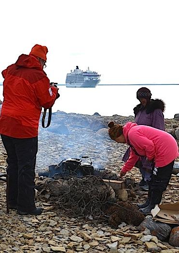 As a passenger from The World takes photos, Eva Otokiak and Mary Avalak tend to a fire Aug. 30 with The World in the background. (PHOTO BY PAUL BILLOWES/ KITIKMEOT HERITAGE SOCIETY)