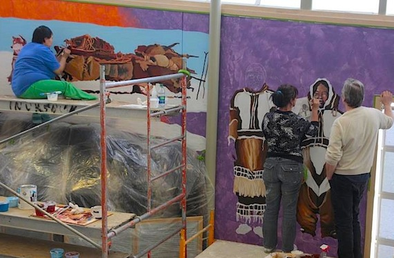 Mural artist Ele Davis from Calgary, centre, works with local artists on a mural in Cambridge Bay's May Hakongak Library and Cultural Centre which commemorates the 100th anniversary of the Canadian Arctic Expedition. (PHOTO COURTESY OF THE KITIKMEOT HERITAGE SOCIETY)