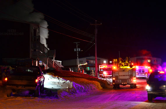 Iqaluit firefighters and other emergency responders work on a fire that broke out around 2:10 a.m. Dec. 21 at building 2245, a 17-unit apartment complex. The blaze damaged three apartment units and multiple families have been left homeless. (PHOTO COURTESY OF AARON WATSON)