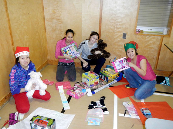 From left to right: Minnie Parr, Moosie Toonoo, Carmen Rowsel and Leeta Qimirpik, some of the young people in Cape Dorset's youth mentorship program, help wrap gifts for kids. All of the items will be packed into gift baskets and delivered to families in need in the community. (PHOTO COURTESY C. WADDELL)