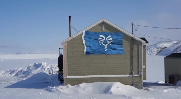 A flag is tacked on to a house in Ivujivik, designer Thomassie Mangiok's home community. (PHOTO COURTESY OF T. MANGIOK)