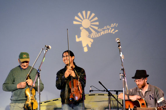 Wesley Hardisty (centre), who's originally from Fort Simpson, NWT, performs during a fiddlers jam held June 29 under the big top tent at the Alianait music festival in Iqaluit. The festival continues through June 30 with a paid concert at Nakasuk School starting at 2:00 p.m. and free activities under the big top tent, workshops at the elders qammaq and an exhibition of the work of Shuvinai Ashoona at the Iqaluit museum. (PHOTO BY JIM BELL)