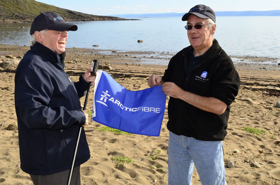 Iqaluit mayor John Graham and Arctic Fibre CEO Doug Cunningham plant the company's flag Aug. 19 near the spot by the Apex beach where Arctic Fibre proposes landing its marine fibre optic cable. (PHOTO BY JIM BELL)