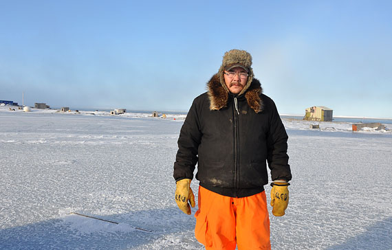 Leo Ikakhik stands by a dog team in the east end of Arviat – a popular attraction for polar bears who can smell the dogs' seal meat. (PHOTO BY SARAH ROGERS)