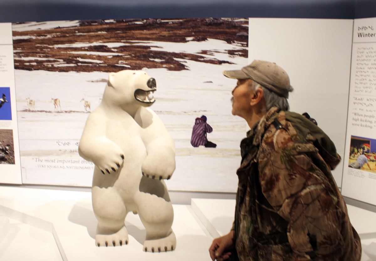Gjoa Haven carver Joseph Suqslaq checks out his polar bear sculpture, one of the many local pieces of art on display at the new Nattilik heritage centre. (PHOTO BY ED STEWART)