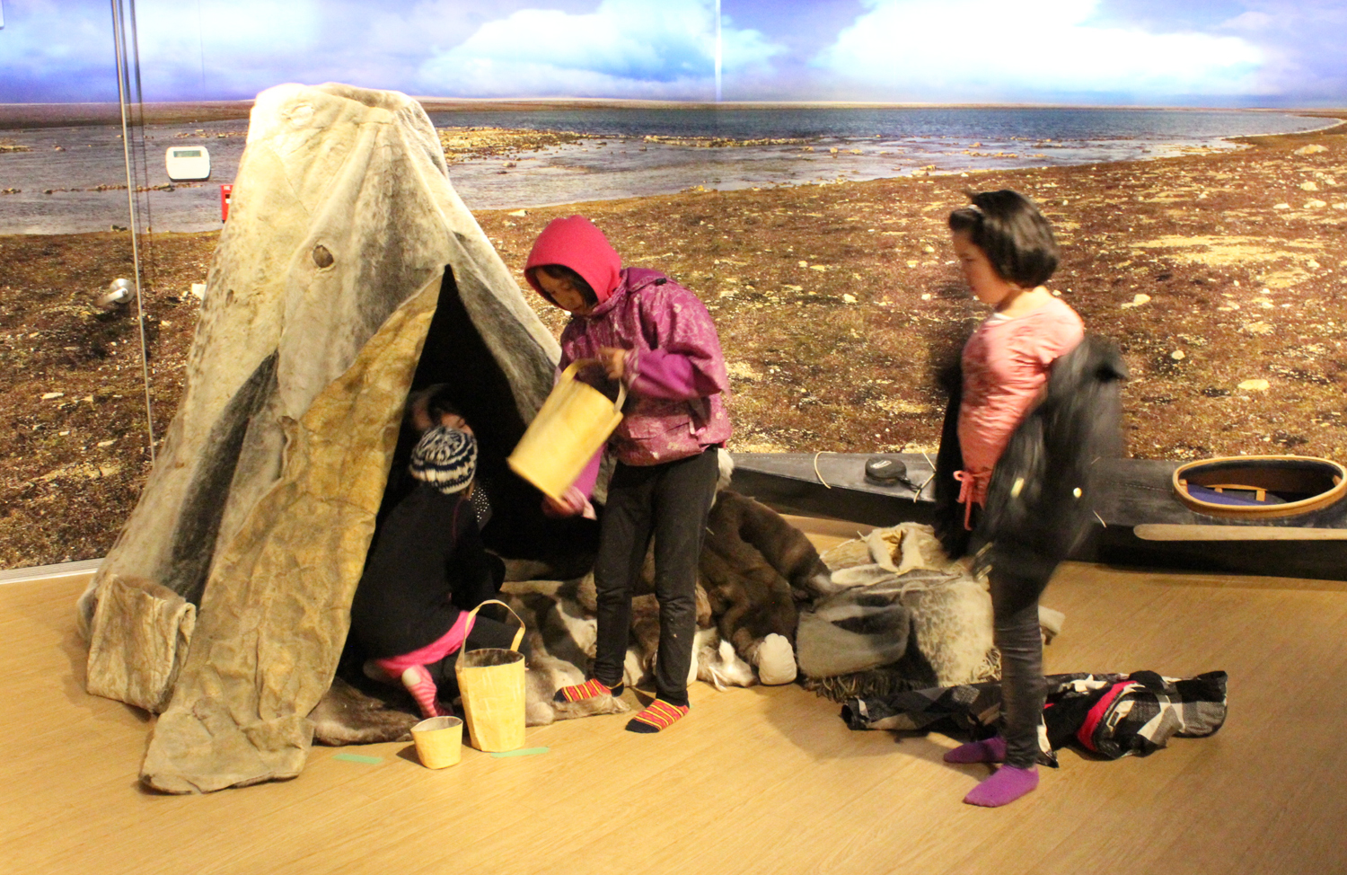 A group of students from Quqshuun Ilihakvik school play around an old skin tent at the Nattilik heritage centre. The traditional  camp scene is designed to encourage interactive cultural learning. (PHOTO BY ED STEWART)