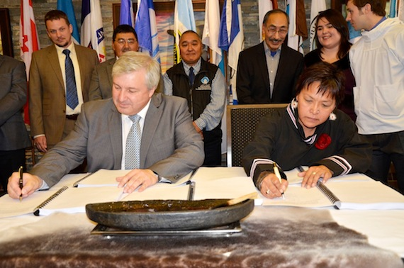 Baffinland president and CEO Tom Paddon, at left and QIA president Okalik Eegeesiak sign an Inuit impact and benefit agreement for the Mary River project last September in Iqaluit. (FILE PHOTO)