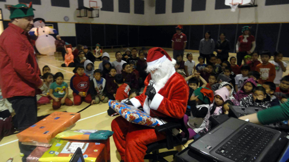 Santa hands out presents to homeroom teachers following a breakfast in the school gym Dec. 17. (PHOTO COURTESY OF THE KSB)