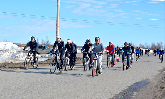 Mental health advocate Clara Hughes, a former Olympian cyclist and speed skater, rides through Kuujjuaq April 30, accompanied by KRPF cadets and other Nunavimmiut youth. As part of her 12,000-kilometre, 95-community tour called Clara's Big Ride, Hughes is cycling across the country to try to remove the stigma that surrounds mental illness. Hughes heads to Iqaluit May 1. (PHOTO BY ISABELLE DUBOIS)