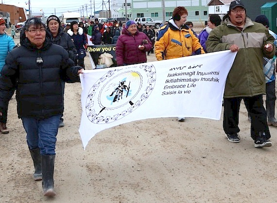 Two marchers carry an Embrace Life banner and small candles during a World Suicide Prevention Day walk in Cambridge Bay last September. Inuit Tapirrit Kanatami is now working to develop an Inuit-specific suicide prevention strategy. (PHOTO BY RED SUN PRODUCTIONS)