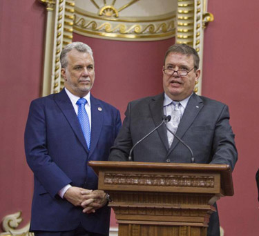 Ungava MNA Jean Boucher, right, takes his oath as a new member of Quebec's National Assembly April 17, flanked by Premier Philippe Couillard, at left. (FILE PHOTO)