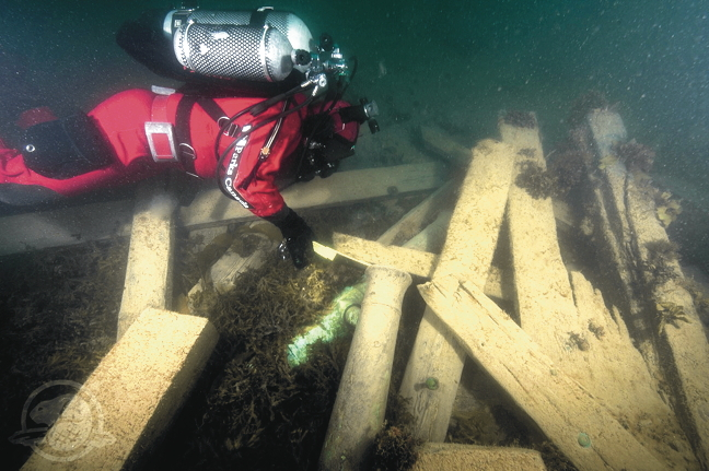 Parks Canada underwater archaeologist Filippo Ronca measures the muzzle bore diameter of a brass cannon on the HMS Erebus shipwreck in Queen Maud Gulf, late-September 2014. (COURTESY OF PARKS CANADA)