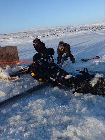 Two Salluit hunters help haul a skidoo out of a lake about 130 kilometres east of the Nunavik community Jan. 10. (PHOTO COURTESY OF C. IKEY)