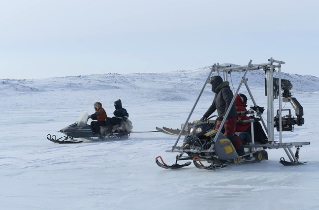A camera crew, led by director Kim Nguyen, shoots a snowmobile in motion, piloted by characters Lucy and Roman in the feature film
