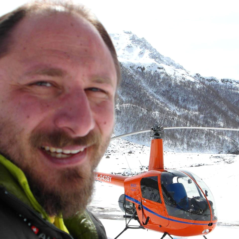 The globe-trotting Russian pilot Sergey Ananov with his helicopter, a two-seater Robinson R-22. The aircraft went missing July 25 over Davis Strait. Ananov has been found and was taken aboard the CGS Pierre Radisson. (IMAGE FROM R22RTW FACEBOOK PAGE)