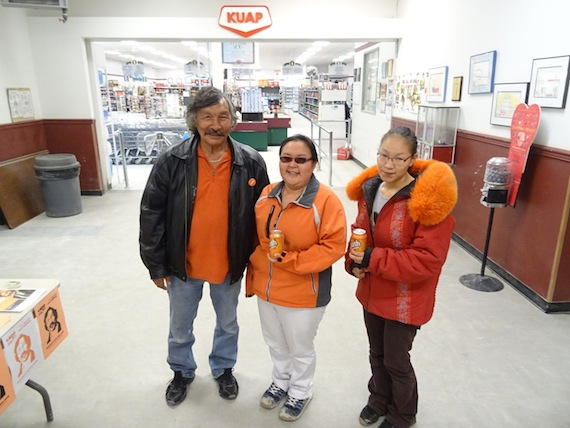 All in orange: Mary Anavilok and Janet Anavilok — who at 18 plans to vote Oct. 19 for the first time — stand with Jack Anawak, the NDP's federal candidate in Nunavut, Sept. 19 in the lobby of the co-op store in the western Nunavut town of Cambridge Bay. (PHOTO BY JANE GEORGE)