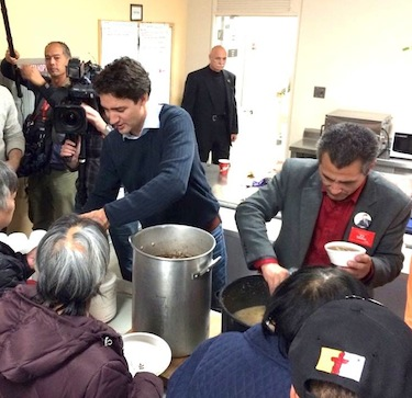 Liberal party leader Justin Trudeau helps serve food, with Liberal candidate Hunter Tootoo, at the Oct. 10 community feast in Iqaluit. (PHOTO BY STEVE DUCHARME)