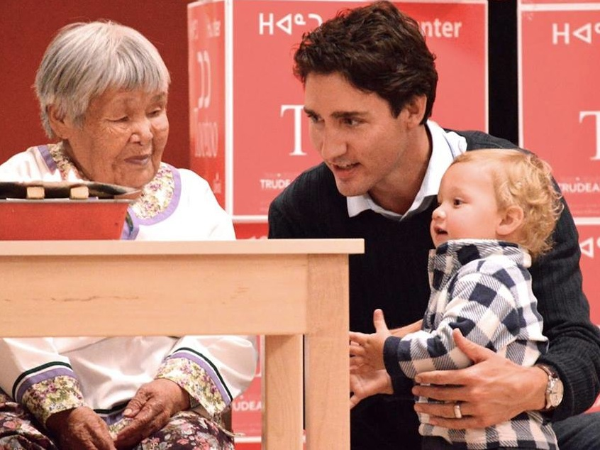 Inuapik Sageaktook, Liberal leader Justin Trudeau, and his 18-month-old son, Hadrien, by the qulliq, Oct. 10, at the community feast in Iqaluit. (PHOTO BY STEVE DUCHARME)