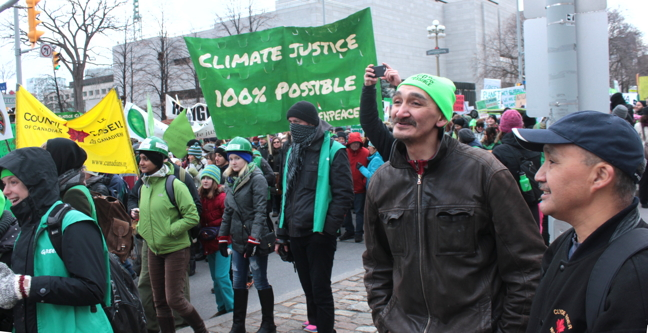 Jerry Natanine, in green tuque, with a friend from Clyde River Elisha Sanguya, in ball hat, take part in a march in Ottawa in support of renewable energy Nov. 29. (PHOTO BY LISA GREGOIRE)